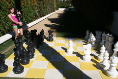 Big Chess Game. Girl holding a giant chess piece Stock Images