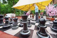 Big chess pieces on chessboard in park and chindren moving chess. Pieces. Focus on chess stock images