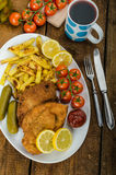 Big Chicken schnitzel with homemade chilli french fries Royalty Free Stock Photography
