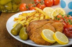 Big Chicken schnitzel with homemade chilli french fries Stock Photo