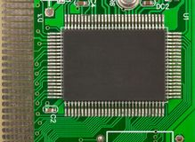 Big chip on the green PCB. There are a lot of legs of this chip, resistors and other small electronic elements here too Royalty Free Stock Photography