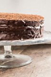 Big chocolate cake on festive glass stand Royalty Free Stock Photo