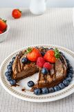 Big chocolate cheesecake with blueberry strawberry raspberry on a round plate. Stock Photo