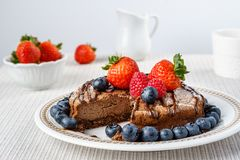 Big chocolate cheesecake with blueberry strawberry raspberry on a round plate. Royalty Free Stock Photos