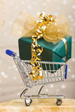 Big christmas gift in shopping cart Stock Image