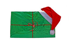 Big Christmas green gift with a cap of Santa Claus. Big Christmas gift in green package with a cap of Santa Claus Stock Photo
