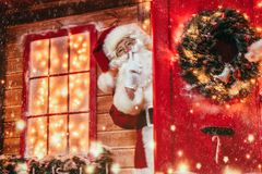 Big christmas secret. Christmas concept. Portrait of a fairytale Santa Claus peek out from behind the door and leaned his index finger to his lips showing a stock photos