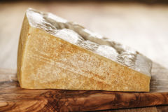 Big chunk of italian parmesan cheese on wooden cutting board Stock Image