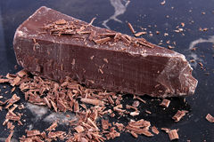 Big chunk of milk chocolate and shavings Royalty Free Stock Photo