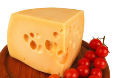 Big chunk of yellow cheese and tomatoes Stock Photography