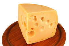 Big chunk of yellow cheese on wood plate Stock Photos