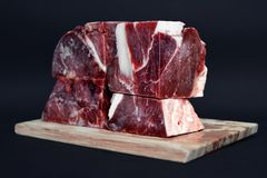 Big chunks of streaky beef meat for raw feeding of cats and dogs on wooden board in front of dark background. Big chunks of streaky beef meat for raw feeding of royalty free stock photo