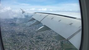 Big city in daytime light under fluffy white clouds in clear blue sky in wonderful aerial view from airplane window wing. Picturesque aerial view from airplane stock video footage