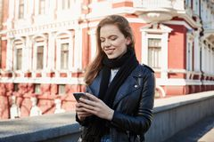 Big city life. Portrait of charming stylish girl standing on street, holding smartphone and texting while on her way to. Cinema. Sister sends her geolocation Royalty Free Stock Photo