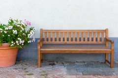 Big clay pot with white and pink flowers and wooden bench against street wall. Gardering design. Patio and relax concept. stock photos