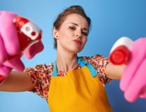 Housewife using bottles of cleaning detergent as guns on blue Royalty Free Stock Image