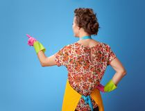 Young woman with rubber gloves pointing at something on blue. Big cleaning time. Seen from behind young woman with rubber gloves pointing at something on blue stock image