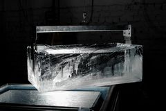 Big clear ice cube in the special holder. On the ice production plant in the dark with the one spotlight Royalty Free Stock Photos