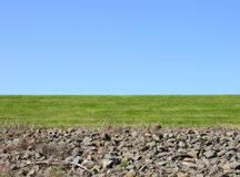 Big clear sky. A view of the sky on a clear day with green grass and rocks in the foreground Royalty Free Stock Photo
