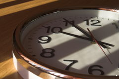 Big clock close-up. Big analog clock close-up in the shadow light on the sun on wooden table Stock Photography