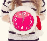 Big clocks a Christmas hat in female hands. New Year. 12 hours. toning Stock Photos