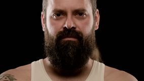 Big close-up of the harsh face of a bearded adult man with brown eyes.  stock video footage