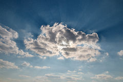 Big clouds on a blue sky with sunbeams Stock Image