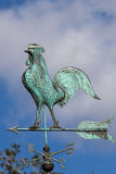 Big cockerel on a weathervane. Metal weather cock pointing north Royalty Free Stock Photo