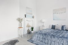 Big comfortable bed with elegant blue bedding, white fireplace portal and flowers in silver vases, real photo with copy space. Concept stock photo
