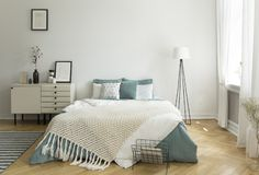 A big comfortable bed with pale sage green and white linen, pillows and blanket in a woman`s bright bedroom interior with windows. Real photo. concept royalty free stock photo