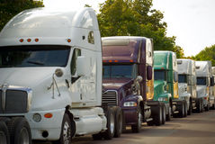 Big commercial transportation trucks lined on road Stock Image