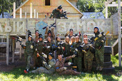 Big company of paintball players and kissing couple Royalty Free Stock Photography