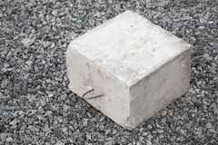 Big concrete construction block. With metal lug on gray gravel Stock Images