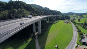Big construction bridge of a highway road. Aerial shoot of a big bridge with highway road in a nature valley and lots of traffic of cars and trucks on a road stock video footage