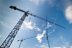 Big construction cranes. With a background of a blue sky with fluffy clouds Stock Photography