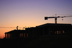 Big construction site. With two cranes at sunset Stock Photos