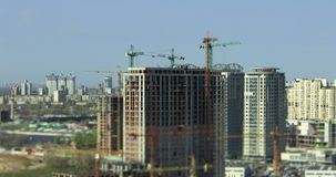 Big construction timelapse tilt-shift. Tilt-shift timelapse with several high-rise apartment houses building with few working cranes in 4K Kiev, Ukraine stock video