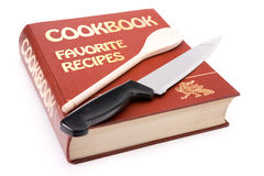 Big cookbook with wooden spoon and kitchen knife. Isolated on white background royalty free stock photography