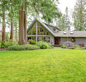 Big countryside house. Beautiful curb appeal. Tile roof countryside house with glass wall, porch and garage. Green lawn together with fir trees and flower bed Royalty Free Stock Image