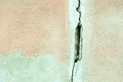 Big crack on the house facade exterior wall and plaster damaged by earthquake. Stock Photo