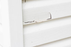 Big crack in the vinyl siding on exterior of house. Close up horizontal close up image of white plastic siding with a big crack in it stock photos