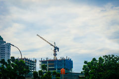 Big crane for building construction with tree and buildings and cloudy sky as background photo taken in Jakarta Stock Images