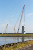 Big crane busy with construction of a new Dutch windturbine Stock Photography
