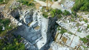 Big crane and a camera hit him in close-up in an open granite quarry at summer sunny day. Aerial view 4k stock video