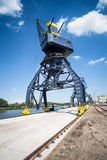 Big crane in the city river port. On the blue sky Stock Photos