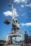 Big crane in the city river port. On the blue sky Stock Images