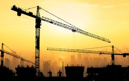 Big cranes and building construction against beautiful dusky sun. Set sky with cityscape in background Stock Photos