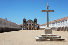 Big cross with church in the background Stock Images