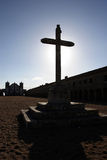 Big cross silhouette and church on second plan. At sunset - in counter light royalty free stock image
