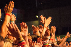 Big crowd clapping with hands in the air at a rock festival. People at a festival wearing wristbands clapping at a festival in front of the big stage where some stock image